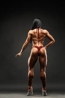 Starkes und muskulöses sportmädchen bei der bikiniaufstellung