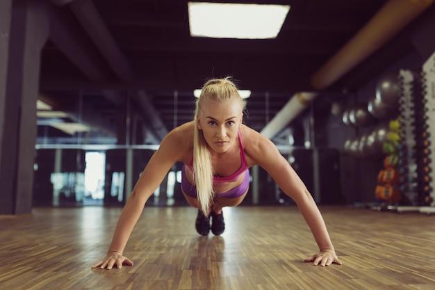 Starkes und schönes athletisches frauentraining in der turnhalle