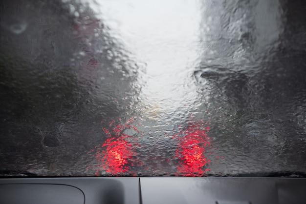 Starkregen. regentropfen auf dem fenster auto. abstraktes unschärfe bokeh des verkehrs- und autolichts.