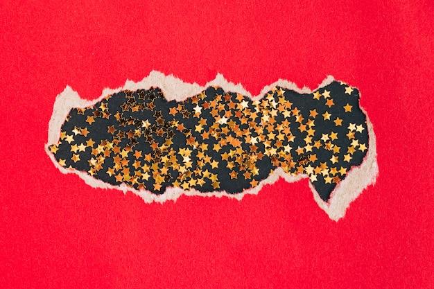 Stars konfettis auf schwarzem hintergrund unter heftigem rotem papier. weihnachtsferien-konzept.