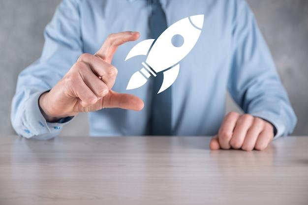 Start-up-konzept mit geschäftsmann hält abstrakte digitale rakete symbol rakete startet und fliegt fliegen