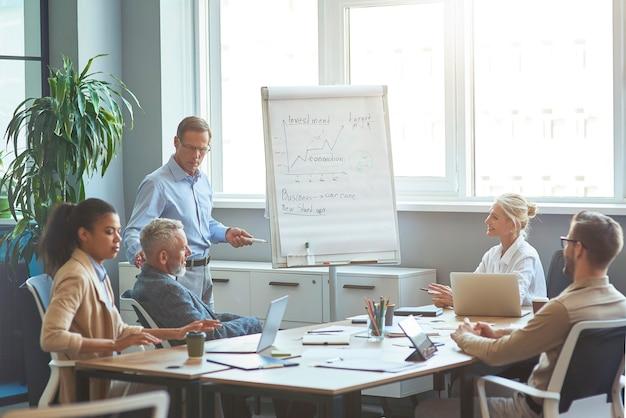 Start-up-team beim brainstorming treffen selbstbewusster reifer geschäftsmann, der in der nähe des flipcharts steht