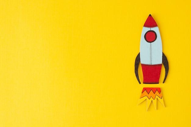 Start-up unternehmen . einkommen, gehalt steigern oder steigern. gezeichnete rakete auf buntem gelb. copyspace.
