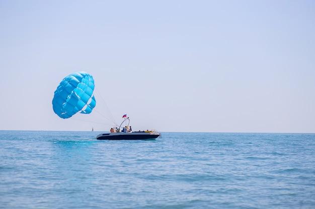 Starten eines fallschirms mit touristen von einem boot mitten im meer. strandaktivitäten zur freien verfügung