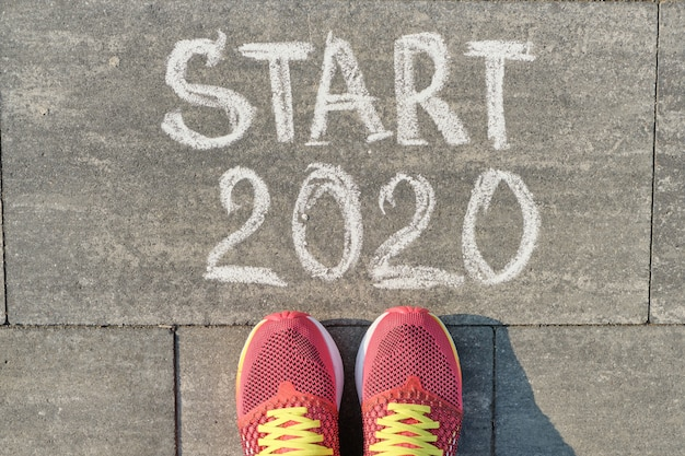 Starten sie 2020, text auf grauem bürgersteig mit den frauenbeinen in den turnschuhen