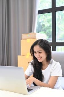 Starten sie eine kleinunternehmerin, die an einem laptop arbeitet und die bestellung im internet in ihrem startup-homeoffice überprüft. online-verkaufs- oder online-shopping-konzept.