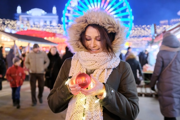 Starten sie neujahr 2021, glückliche frau, die roten weihnachtsball mit text 2021 am weihnachtsmarkt zeigt