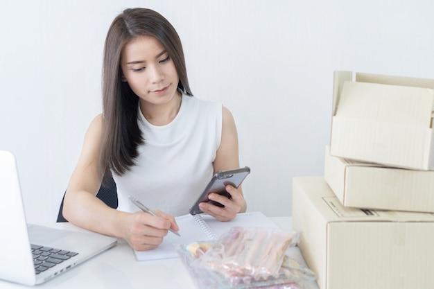 Starten sie oben kleinunternehmer kmu oder freiberuflich tätige frau, die den smartphone verwendet, der zu hause konzept arbeitet