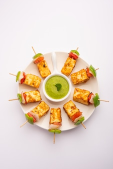 Starter-snack paneer tikka mit stick in teller mit grünem chutney, isoliert auf weiss. indisches gericht mit gegrilltem hüttenkäse mit gemüse und gewürzen