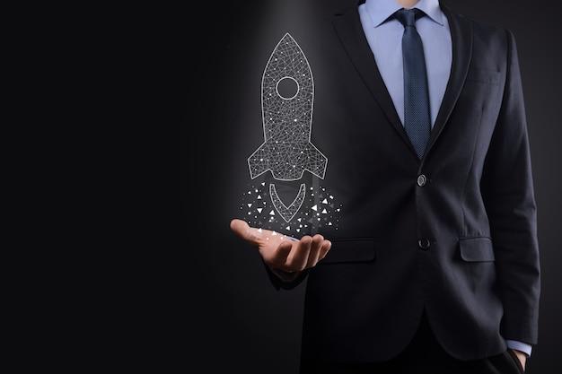 Startgeschäftskonzept, geschäftsmann, der symbol transparente rakete hält, startet und fliegt vom bildschirm mit netzwerkverbindung auf dunklem hintergrund heraus
