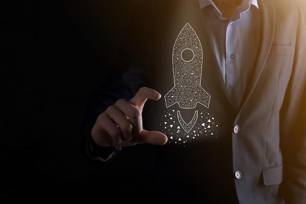 Startgeschäftskonzept, geschäftsmann, der symbol transparente rakete hält, startet und fliegt vom bildschirm mit netzwerkverbindung auf dunklem hintergrund heraus.