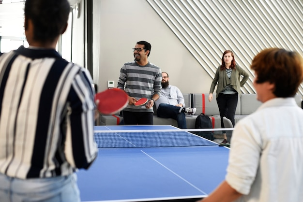 Startgeschäftsleute, die zusammen tischtennis während der abschaltzeit spielen