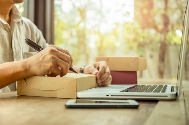 Startgeschäftsmann-schreibenskundenadresse auf paket mit laptop und handy auf tabelle.
