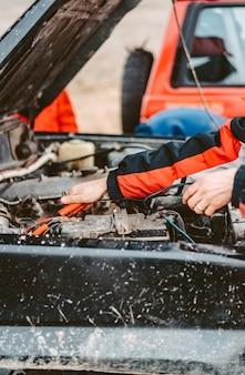 Starthilfe für die entladene batterie mithilfe von überbrückungskabeln.