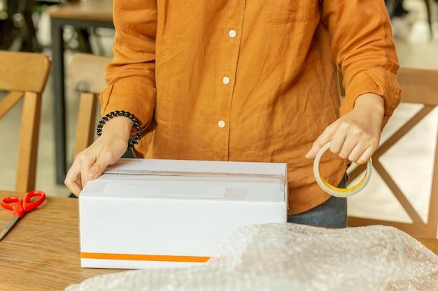 Startinbetriebsinhaberinverpackungspappschachtel am arbeitsplatz.