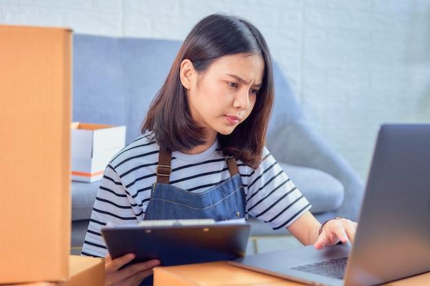 Startkleingewerbe, junger asiatineigentümer überprüfen den kundenauftrag vom computer, verkäufer bereitet den lieferungskasten vor.