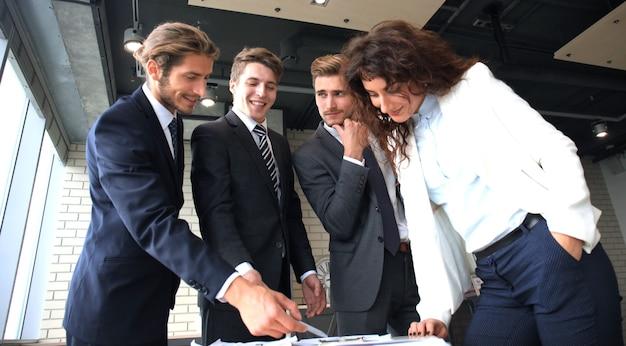 Startup-business-team bei treffen in modernen hellen büroräumen brainstorming, arbeiten an laptop und tablet-computer