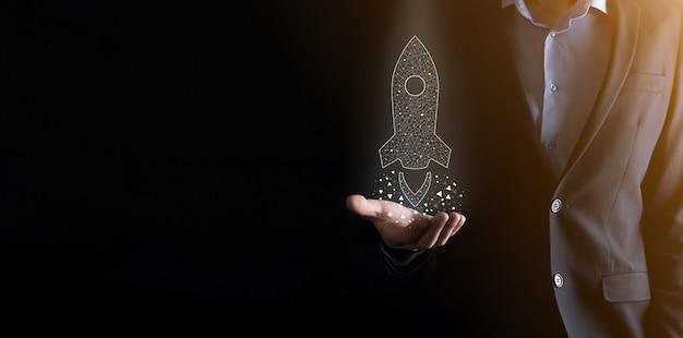 Startup-geschäftskonzept, geschäftsmann, der das symbol transparente rakete hält, startet und fliegt vom bildschirm mit netzwerkverbindung auf dunklem hintergrund.