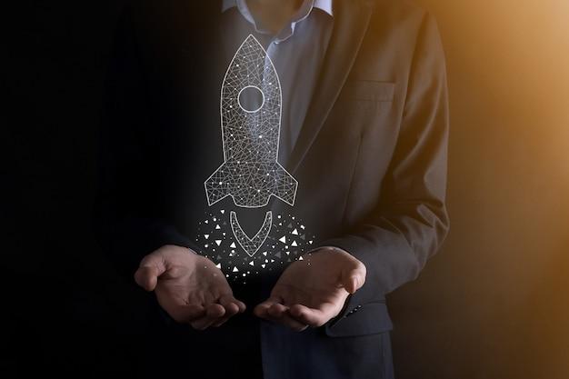 Startup-geschäftskonzept, geschäftsmann, der symbol transparente rakete hält, startet und fliegt vom bildschirm mit netzwerkverbindung auf dunkler wand heraus.