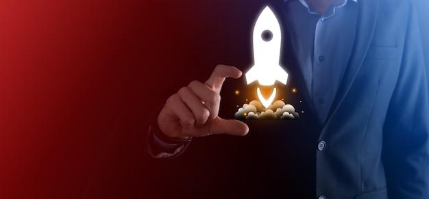 Startup-geschäftskonzept, geschäftsmann, der tablette und symbolrakete hält, startet und fliegt vom bildschirm mit netzwerkverbindung auf dunkler oberfläche heraus