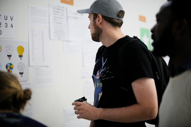 Startup-geschäftsleute, die auf durchdachten informationen des strategie-brettes schauen
