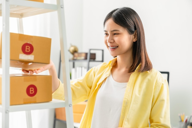 Startup-kleinunternehmen, junge asiatische frau, die kisten für produkte überprüft und verpackt, um sie an kunden zu senden. arbeiten im home office.