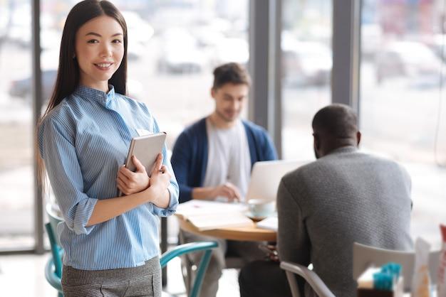 Startup teamer. nette jugendliche asiatische dame, die mit einem buch steht und sich auf hintergrund ihrer arbeitskollegen freut.