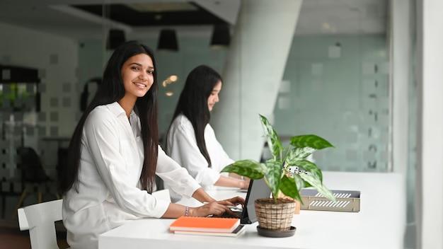 Startup-unternehmensgruppe, die mit digitalem tablett auf weißem schreibtisch im besprechungsraum arbeitet