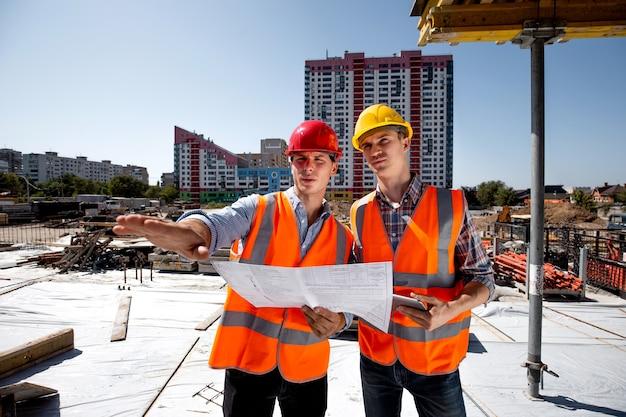 Statiker und architekt in hemden, orangefarbener arbeitsweste und helm besprechen die dokumentation auf der baustelle. .