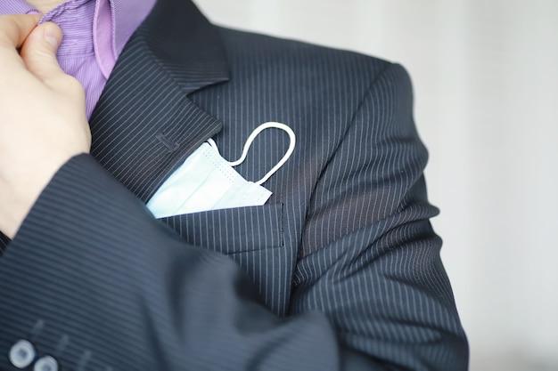 Statt einer serviette ragt eine medizinische einwegmaske aus der tasche. ein mann mit einwegmaske in anzug und jeans. individueller atemschutz.