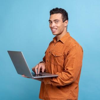 Stattlicher erwachsener mann, der einen laptop anhält