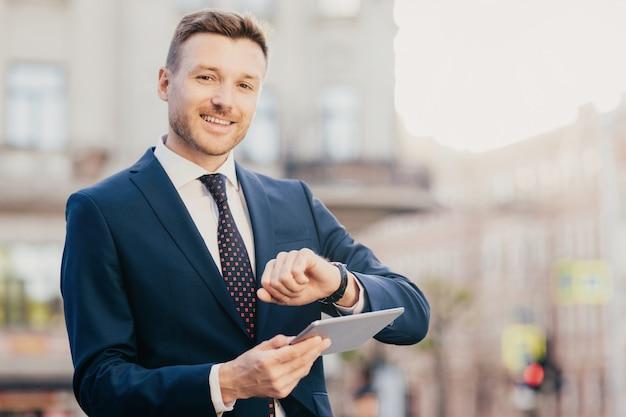 Stattlicher männlicher unternehmer kommt auf das treffen mit geschäftsleuten