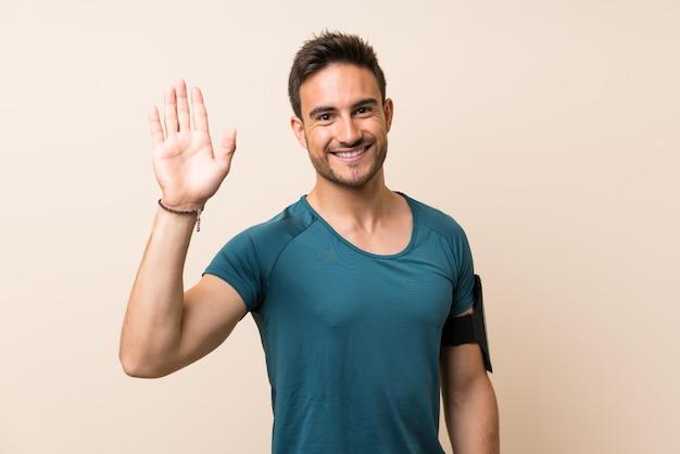 Stattlicher sportmann über getrennter begrüßung mit der hand mit glücklichem ausdruck