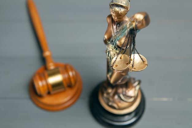 Statue der gerechtigkeit und hammer des richters auf grauem hintergrund