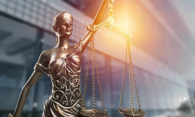 Statue der justizfrau mit waagennahaufnahme auf dem hintergrund des justizgebäudes