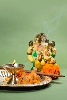 Statue des hinduistischen gottes ganesha mit anbetungsanordnung auf grüner oberfläche.