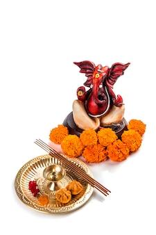 Statue des hinduistischen gottes ganesha mit anbetungsanordnung auf weißer oberfläche.