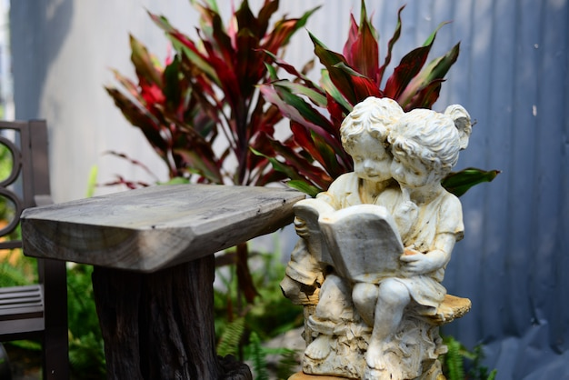 Statue des mädchens und des jungen, die das buch im garten lesen