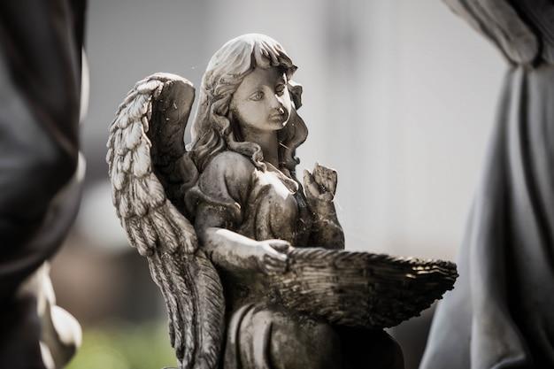 Statue eines engels, der korb im garten hält