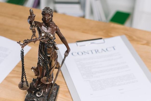 Statue von gerechtigkeit über der tabelle mit vertragspapier