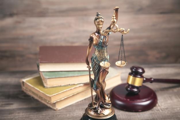 Statue von lady justice, buch und hammer.