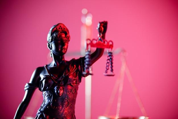 Statue von lady justice im notariat in rotem neon. symbol für gerechtigkeit und gesetz.