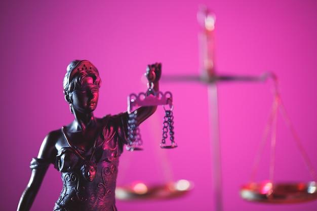Statue von lady justice in lila neon. symbol für gerechtigkeit und gesetz.