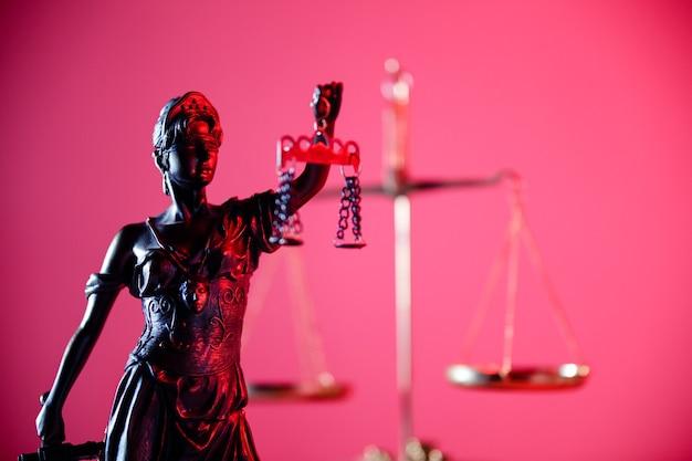 Statue von lady justice in rotem neon. symbol für gerechtigkeit und gesetz. nahansicht.