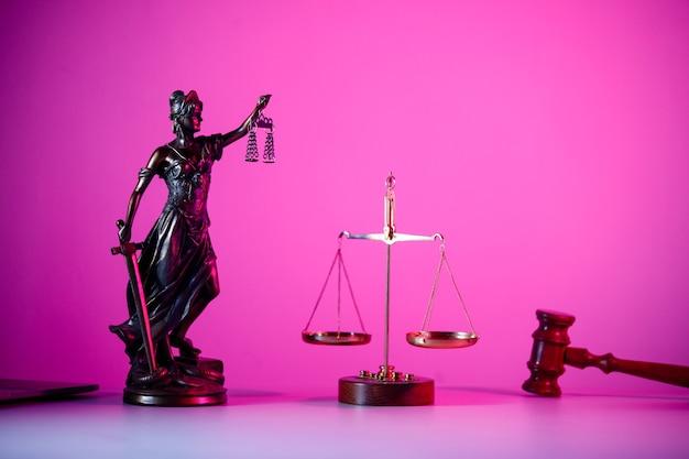 Statue von lady justice mit schuppen in lila neon. symbol für gerechtigkeit und gesetz.