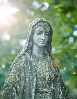 Statue von maria, mutter gottes, am hintergrund des herbstbaums