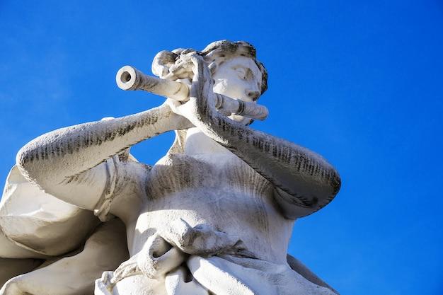 Statue weißer stein der musikerin mit pfeife im belvedere-barockgarten, wien, österreich