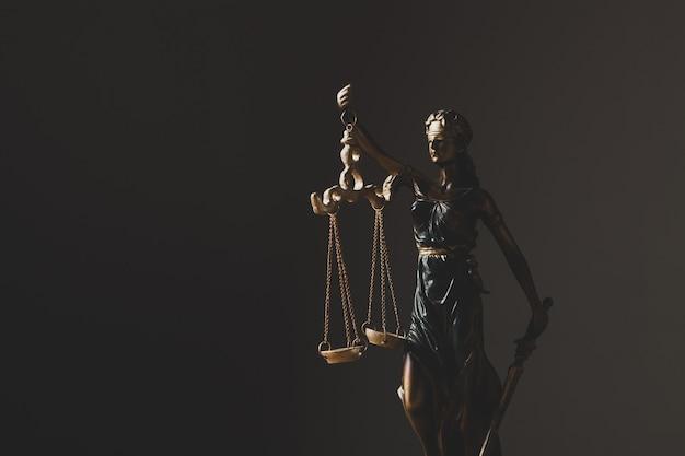 Statuette der frauenjustiz auf einer dunklen szene