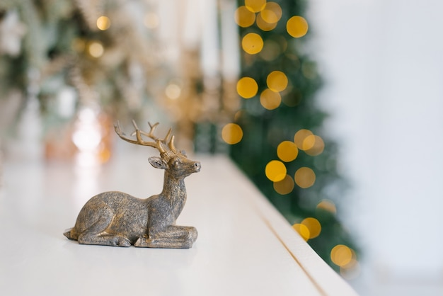 Statuette eines hirsches auf dem hintergrund der weihnachtsbeleuchtung. neujahrskarte mit kopierplatz