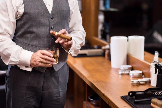 Statussymbol. nahaufnahme des reichen mannes, der luxusanzug trägt, der mit whiskyglas und zigarre am friseursalon steht